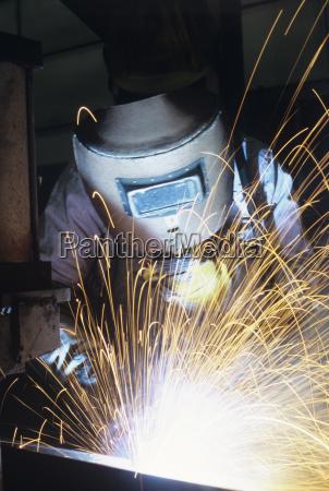 welder wearing protective face mask welding