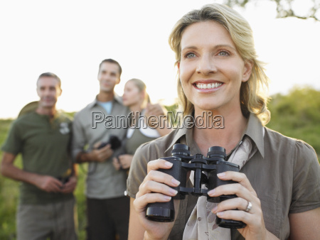 happy woman holding binoculars with friends