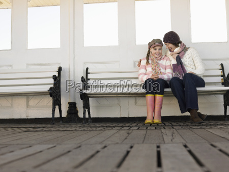 mother and daughter sitting on pier