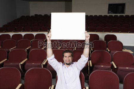 male student raising sign board while