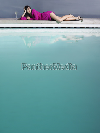 woman reclining by pool with champagne