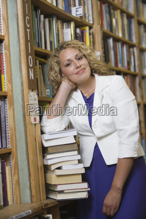 female librarian standing by stack of