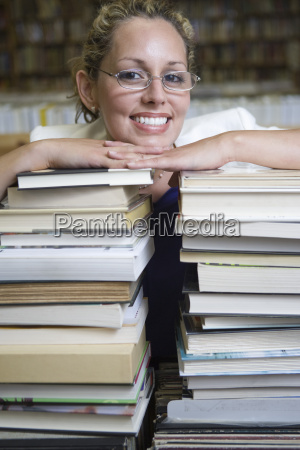 happy female librarian leaning on stack