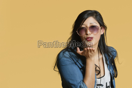young woman blowing kisses over colored