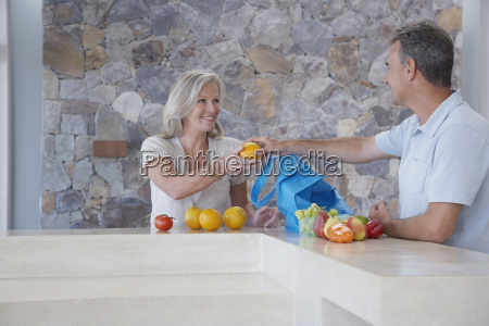 man handing fruit to woman at