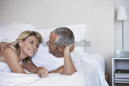 affectionate couple relaxing on bed