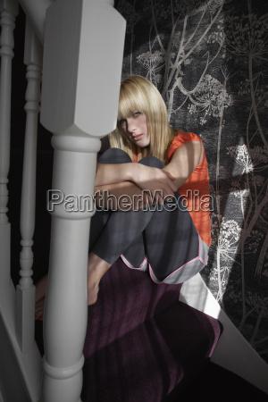 lonely teenage girl hugging knees on