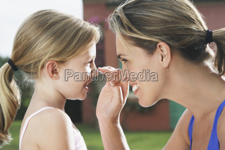 mother applying sunscreen to girls nose
