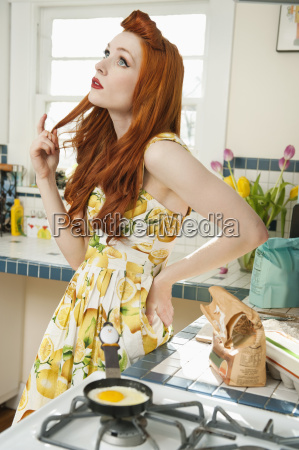 young woman at kitchen counter thinking