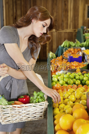 beautiful young woman selecting fruit in