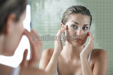 woman examining herself in front of