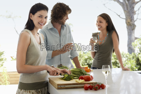 woman chopping vegetables with friends communicating