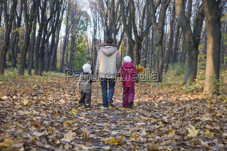 mother and children walking in park