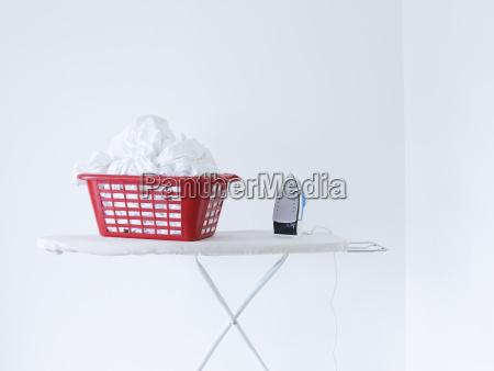 iron and laundry basket on ironing