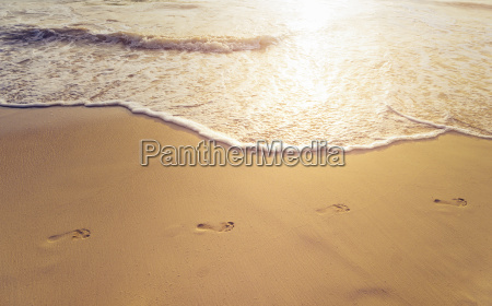 beach wave and footprints at sunset