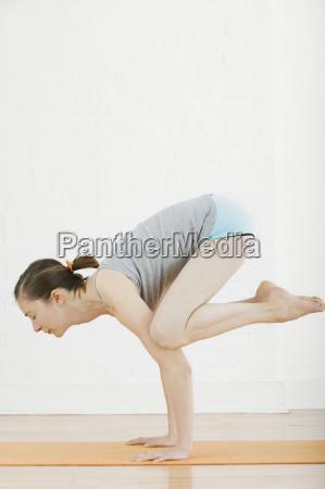 woman practicing yoga in crane pose