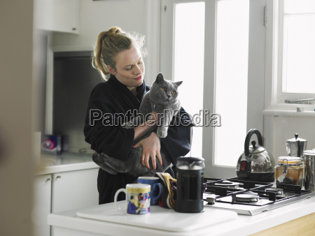 woman holding cat in domestic kitchen