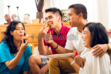 asian people eating pizza at party