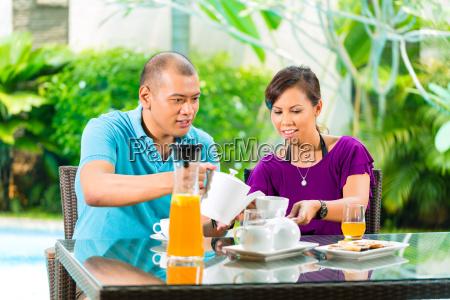 asian couple having coffee on home