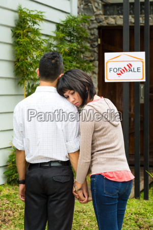 disappointed asian couple in front of