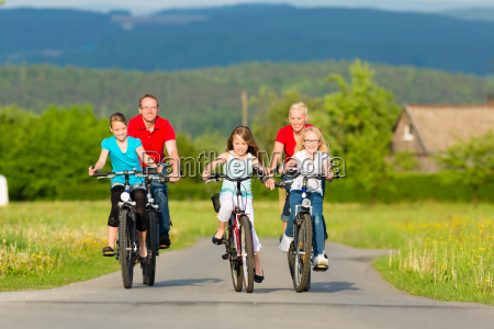 family with kids cycling in summer