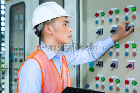 asian technician at panel on construction