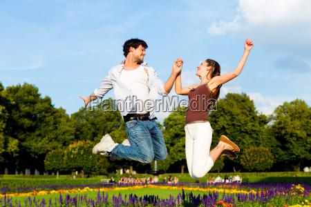 tourist couple in city park jumping