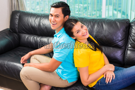 young asian couple on sofa or
