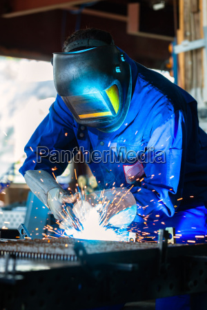 welder welding metal in workshop with
