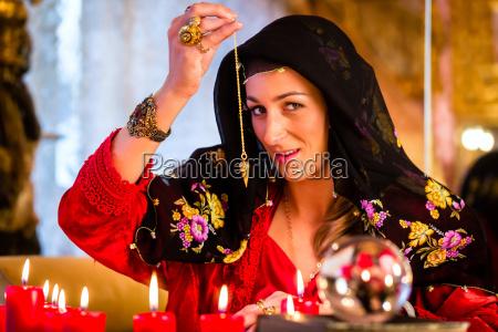 radiesthesist in seance dowsing with pendulum