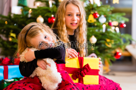 children receiving presents on christmas day