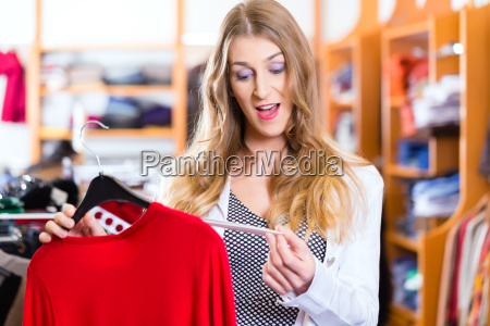 woman shopping clothes in shop or