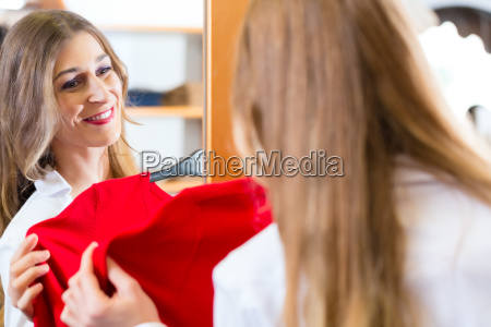 woman trying fashion clothes in shop