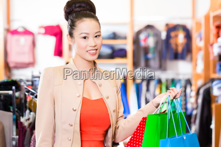 asian woman with shopping bags in