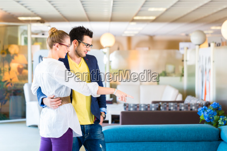 couple buying couch in furniture store