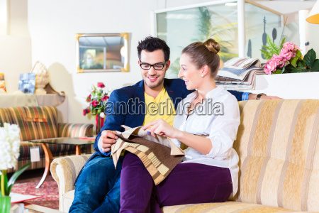 couple picking couch seat cover in