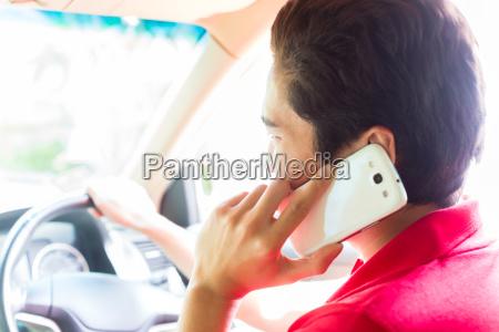 asian man telephoning while driving car