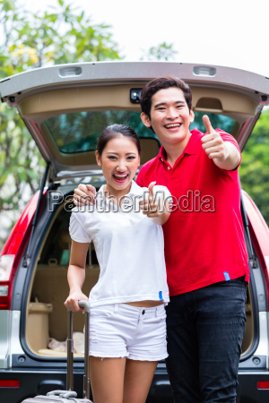 asian couple travelling with new car
