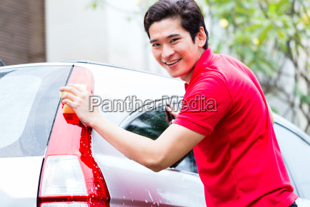asian man cleaning and washing car