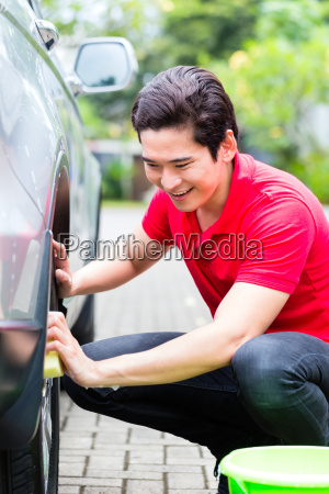 asian man cleaning car rims with
