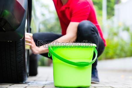 man cleaning wheel rim while car