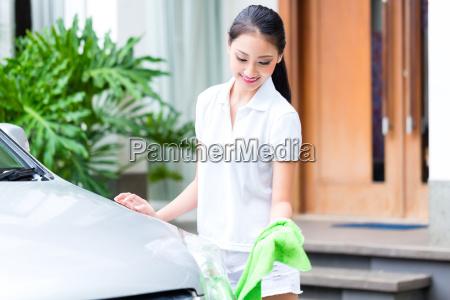 asian woman cleaning headlamp at car