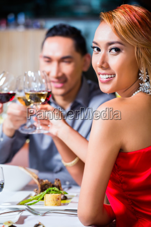 asian friends dining in fancy restaurant