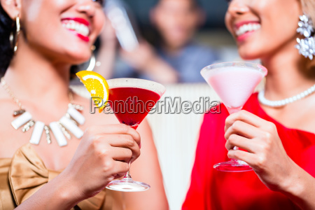 asian women drinking cocktails in fancy