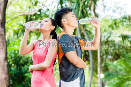 asian couple drinking water after sport