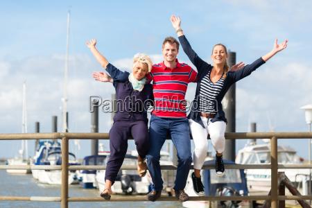 friends sitting at marina pier