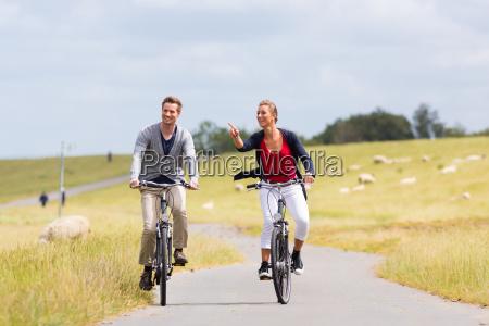 couple having sea coast bicycle tour