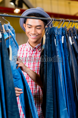 asian man browsing jeans in fashion