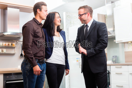 couple consult salesman for domestic kitchen
