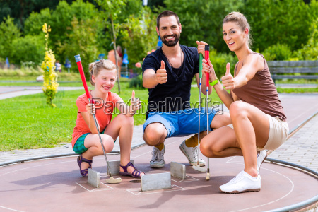 family playing miniature golf on summer